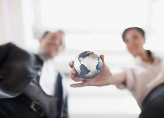 Businesswoman holding small globe in office
