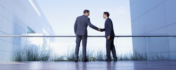 Businessmen shaking hands on balcony