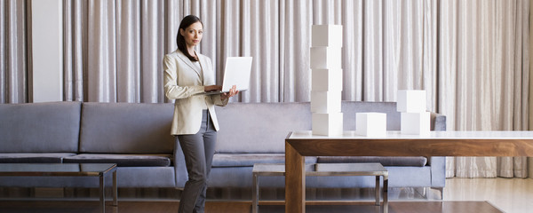 Businesswoman stacking white cubes in hotel lobby