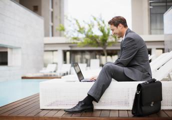 Businessman using laptop on lounge chair near swimming pool