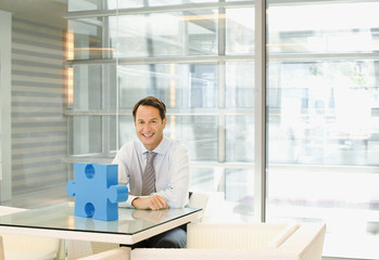 Businessman sitting at desk with jigsaw puzzle piece