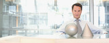 Businessman sitting at desk with sphere and cone