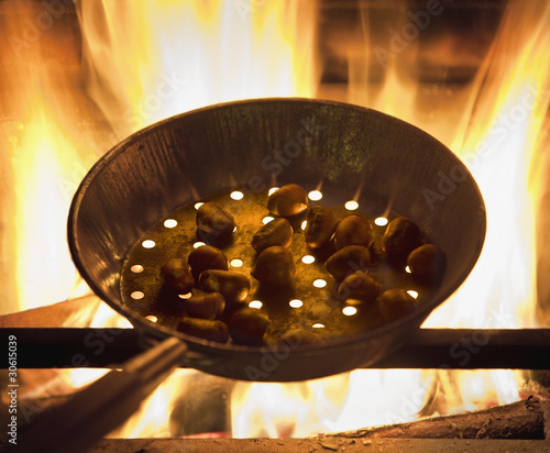 Chestnuts roasting in a pan on fire