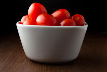 A bowl of cherry tomatoes on a wood table