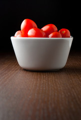 A bowl of cherry tomatoes on a wood table.