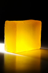 Yellow handmade soap in darkness. Backlit