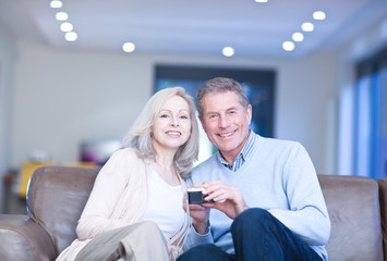Smiling couple holding digital camera on couch