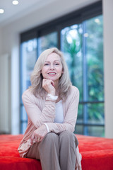 Smiling mature woman sitting on futon