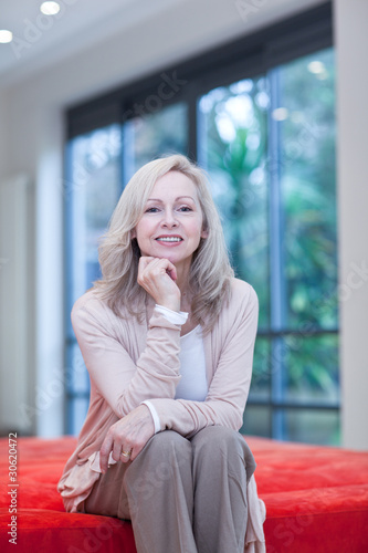 Smiling mature woman sitting on futon