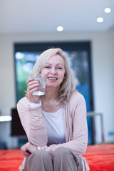 Smiling mature woman holding glass of water