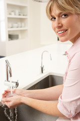 Woman Washing Hands At Kitchen Sink