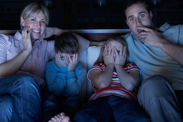 Family Watching Scary Programme On TV Sitting On Sofa Together
