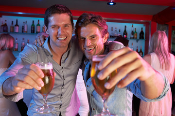 Two Young Men Having Fun In Busy Bar
