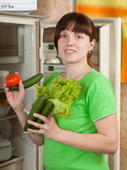 woman putting fresh vegetables   into refrigerator