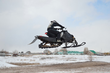 Russia, Samara. Snowmobile rider flying high air