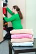 Stack of garments and young woman arranging things in wardrobe