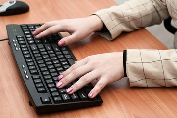 Female hands typing on a black keyboard