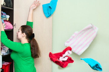 Young caucasian woman throwing clothes from wardrobe back