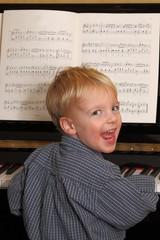 Fröhlicher Junge spielt Klavier