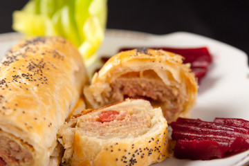 Roll of spicy sausage in flaky pastry