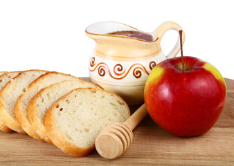 honey in a jug and loaf apple on board