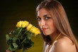 Beautiful woman with a bouquet yellow rose flowers