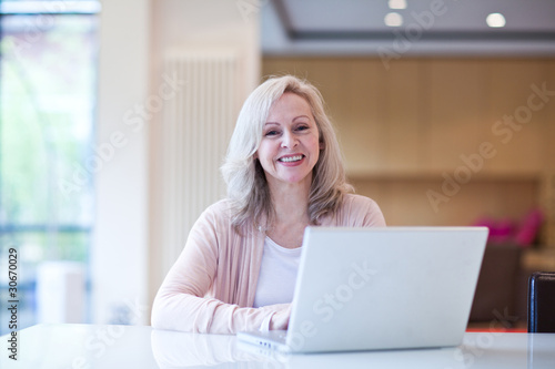 Smiling mature woman using laptop at table