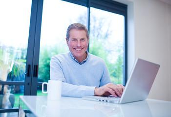 Smiling man using laptop at table