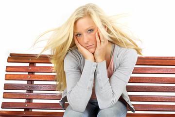 traurige junge Frau auf der Parkbank