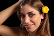 Beautiful woman with a yellow rose in hair