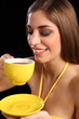 Beautiful smiling woman drinking cup of black tea