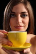 Beautiful woman holding yellow tea cup and saucer