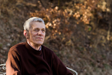 nice elderly white-haired man in a autumn park