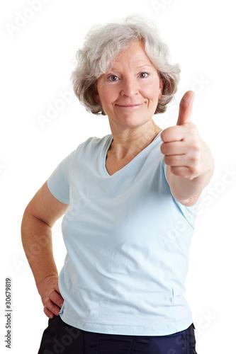Sportliche Seniorin hält Daumen hoch