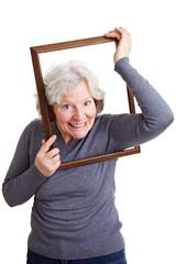 Seniorin klettert durch Rahmen