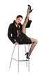 Girl in black suit sitting on stool take leg up.