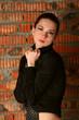 Girl in black suit posing at brickwall.