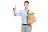 Shocked man looking at store receipt and holding a grocery bag poster