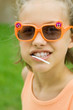Girl wearing sunglasses, lollipop in mouth, portrait