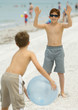 Boys playing with ball on beach