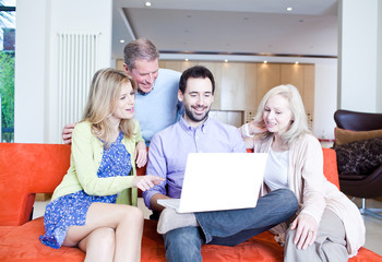 Man using laptop on couch surrounded by wife and parents