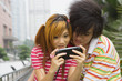 Young couple playing portable video game