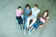 Four teen friends sitting on cushions on ground, looking at camera, high angle view