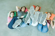 Four teen friends lying on backs on floor, holding up legs, focus on soles of shoes