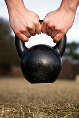 Closeup of hands lifting a heavy kettlebell