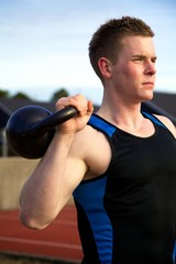 Young man doing kettlebell exercise outside