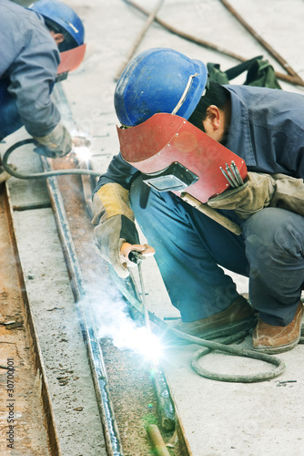 Worker using welding torch at construction site, side view