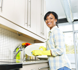 Happy young woman washing dishes