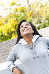 Smiling young woman outdoors looking up
