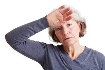 Seniorin hält Hand an die Stirn